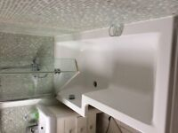 L-shaped bath, shower screen, wash basin, vanity unit and sensor mirror