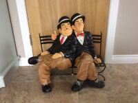 Laurel and Hardy sitting on a park bench