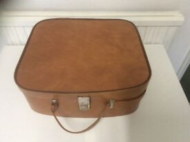 Vintage leather effect tan coloured vanity case with red lining.