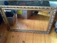 Large mirror with ornate gold coloured frame