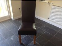 Solid Oak table with six dark brown leather chairs with detailed stitching.