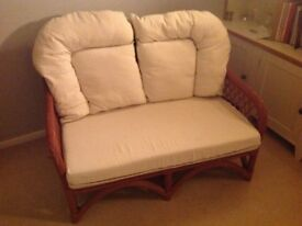Two seater wicker sofa with white upholstery in good condition.