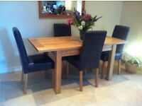 Lovely solid wood extendable dining table with 4 black leather dining chairs