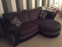 Black/Grey Three seater sofa with leg rest at one side including two matching patterned cushions.