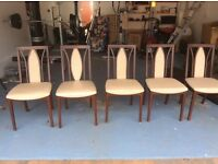 Five wooden, padded dining chairs