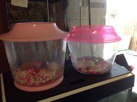 Two pink goldfish tanks , bowls