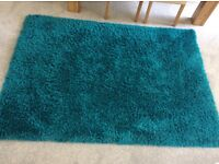 Teal rug, cushion covers and throws