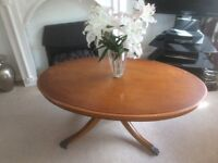 Art deco styled oval coffee table with four legs and casters beautifully decorated feet