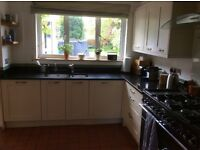High-end kitchen-Ivory coloured cabinets-Black granite work tops-A twin basin Sink.