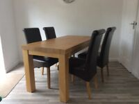 Solid oak dining table and 4 brown leather scroll back chairs in great condition