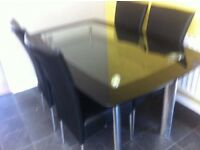 Black an clear glass table an four black chairs