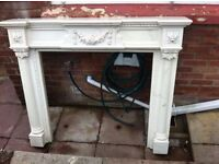 TWO FIRE SURROUNDS 1 LARGE MEXICAN PINE WOODEN SURROUND, 1 MARBLE RESIN ORNATE SURROUND.