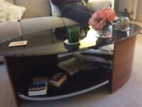 Oval coffee table with black glass 4ftx2ft2ins widest point.wood surround.as seen.