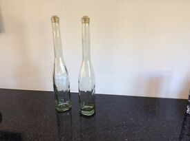 Two tall glass display bottles
