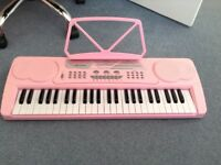 Pink electronic keyboard with adaptor.