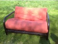 Orange rust coloured sofa bed with black metal frame