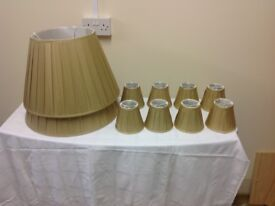 Two gold coloured silk lamp shades and eight small gold coloured silk lamp shades, as new.