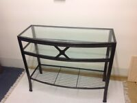 Console table with metal frame and glass top and shelf.