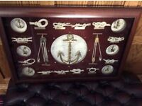 Framed picture featuring knots and anchors. Glass front wood frame.