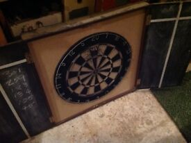 Two dart boards. One in cabinet.