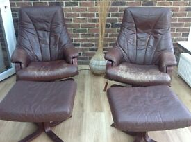2 brown leather swivel armchairs with foot rests
