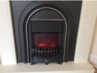 Flame effect electric fire with white mantle surround.