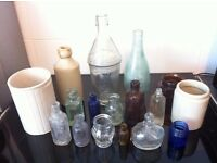 Collection of small and large old bottles and ceramic jars.