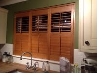 Wooden window shutters folding into 3 sections, 2 natural wood colour, 1 white.