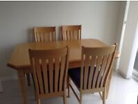 Solid oak extendable dining table with six matching chairs
