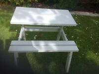 Wooden children's picnic table with attached bench.