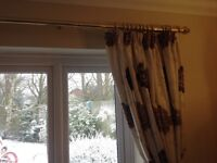 Gold coloured extending curtain poles with draw chord.