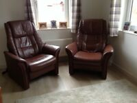 Two brown leather recliner armchairs