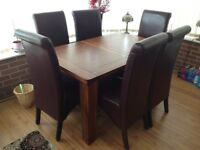 Extending dining table with 6 upholstered chairs.
