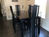 Black glass extending table with six chairs, excellent condition