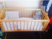 Wooden swinging baby crib comes with sheets and bedding