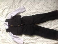 Boys three piece black, pinstripe suit with purple spotted shirt and tie