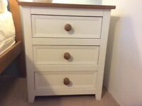 Cream bedside cabinet with 3 drawers and a wood top