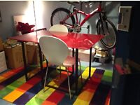 Red glass top dining room table from habitat. Metal legs. Two white stylish chairs