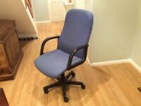 Swivelling and reclining blue fabric desk chair, height adjustable on casters.