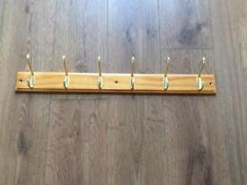 Brass coat hangers x6 on wood