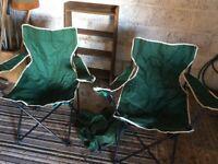 2 dark green folding chairs