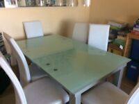 Glass dining table extends to seat 8 and 8 white faux leather chairs