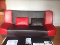 Leather sofa bed with matching cushions