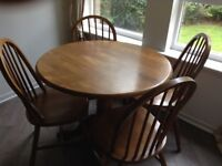 Wooden round table with four wooden chairs.