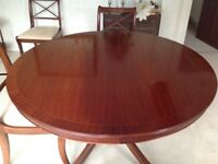 Dining table with six chairs. The tale is round veneer extending to long oval