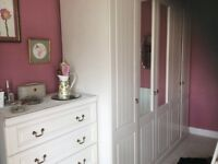 Double wardrobe with mirrored doors and matching chest of drawers