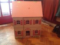 Dolls House with loads of wooden furniture and figurines.