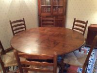 Solid oak dining room table and six ladder back rush seat chairs.