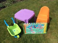 Plastic purple table with 4 plastics orange chairs and a hop scotch foam game and wheel barrow