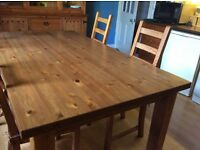 Lovely pine table with four chairs. Big enough to seat 6 - 8 people. In excellent condition.